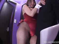 An Asian girl in a playboy bunny costume sucks a dick